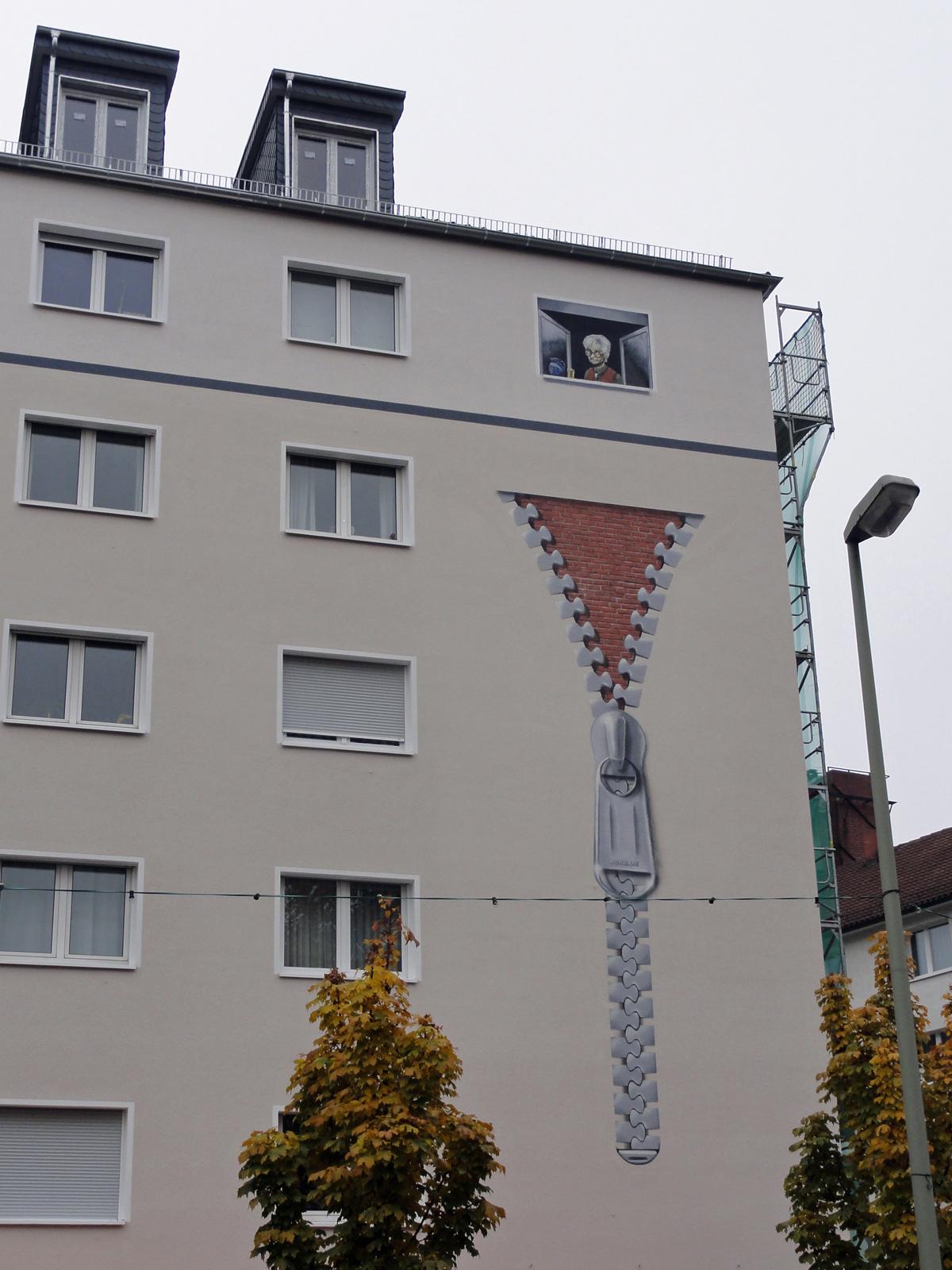 Reißverschluss an der Hausfassade am Merianplatz