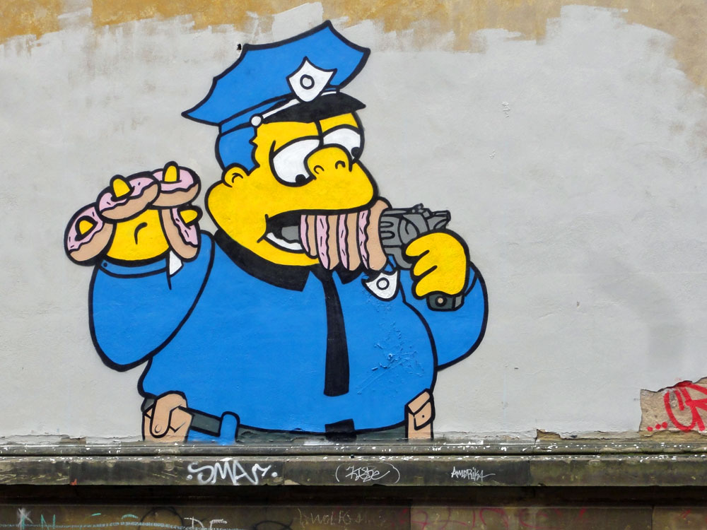 Simpsons-Cop with gun and donuts