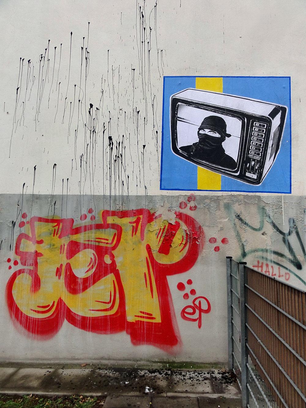 Streetart in Frankfurt: Paste Up mit vermummten Mann im Fernseher