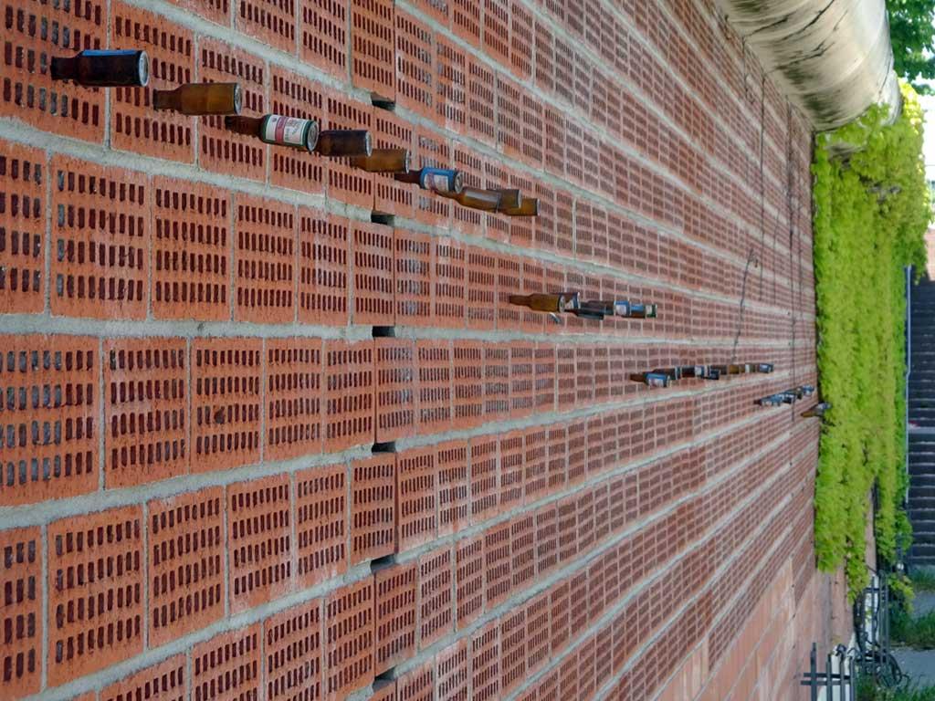 Flaschensammlung entlang der Wand am Hafentunnel
