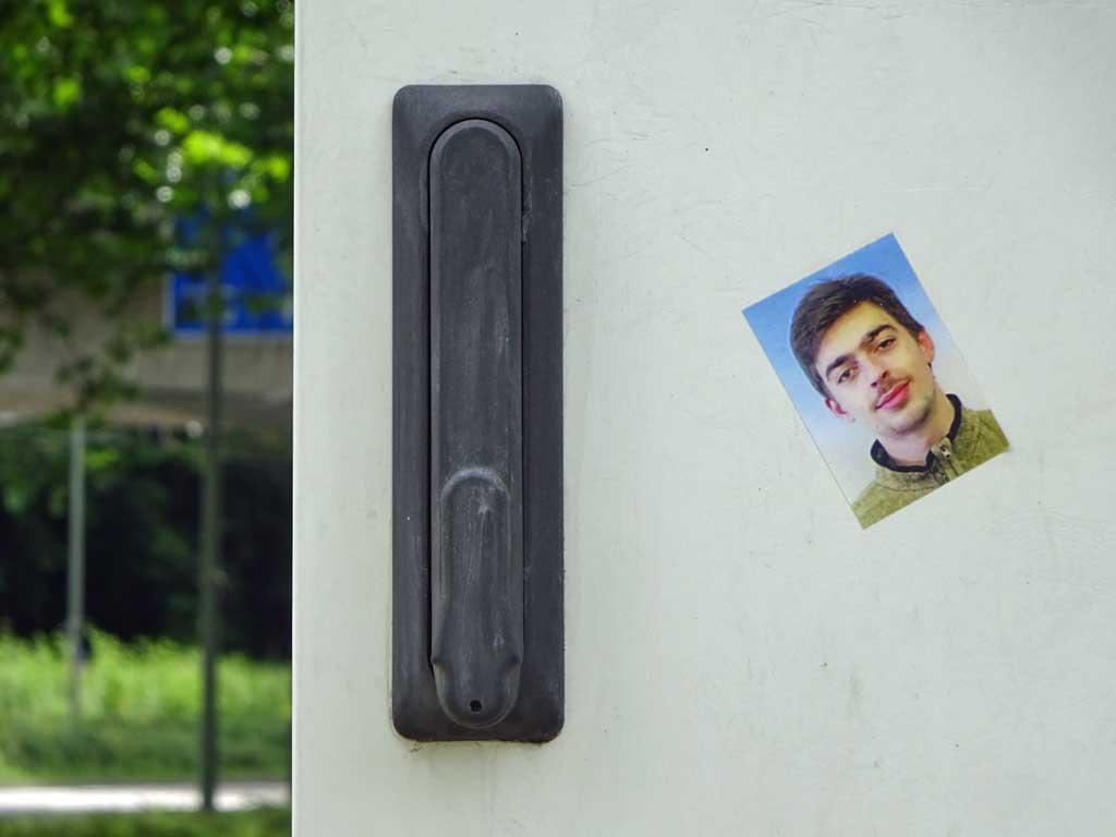 Aufkleber in Frankfurt Passfoto eines jungen Mannes