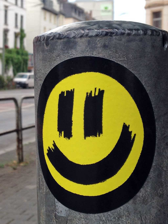 Aufkleber in Frankfurt - Gelb-schwarzer Smiley