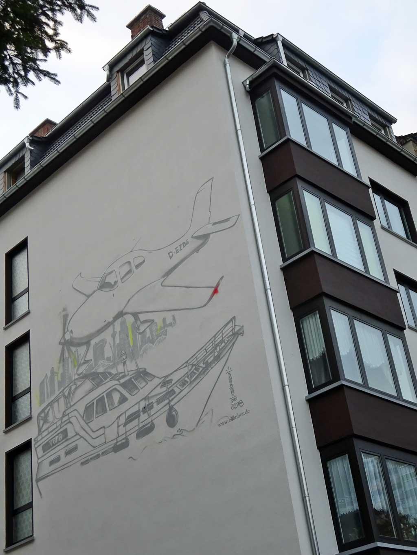 Graffiti-Wandbild mit Flugzeug und Schiff von Bomber