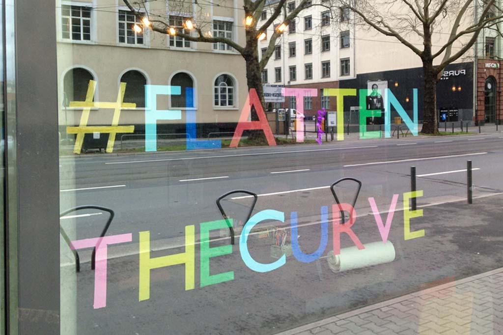 Corona in Frankfurt - Schaufenster mit #FlattenTheCurve in bunten Buchstaben