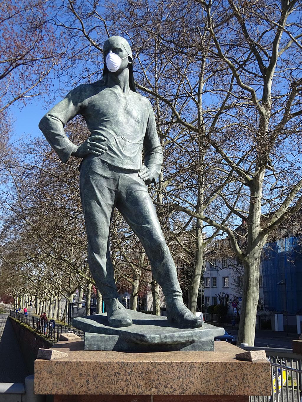 Corona in Frankfurt - Hafenarbeiterskulptur mit Schutzmaske an der Friedensbrücke