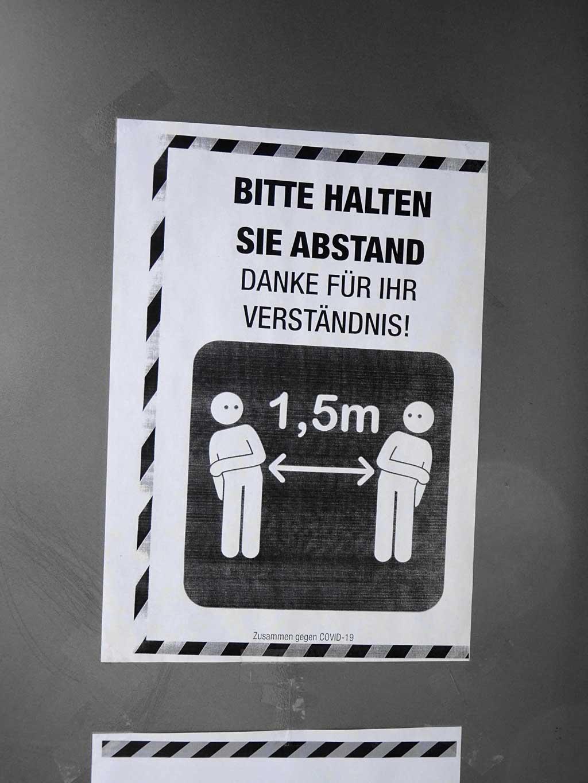 """Zettel """"Bitte halten Sie Abstand"""" mit zwei voneinander wegbewegenden Menschen"""