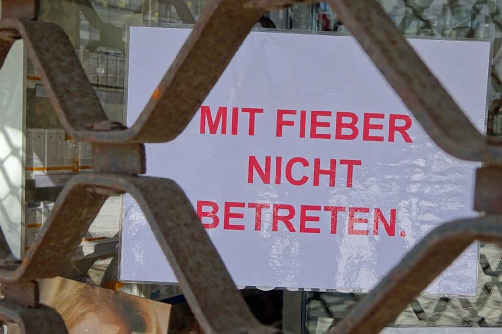 Laminierter Zeittel an Apotheke: Mit Fieber nicht betreten