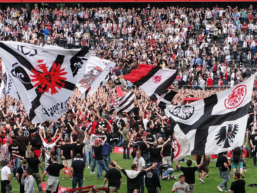 Fans von Eintracht Frankfurt feiern auf dem Spielfeld