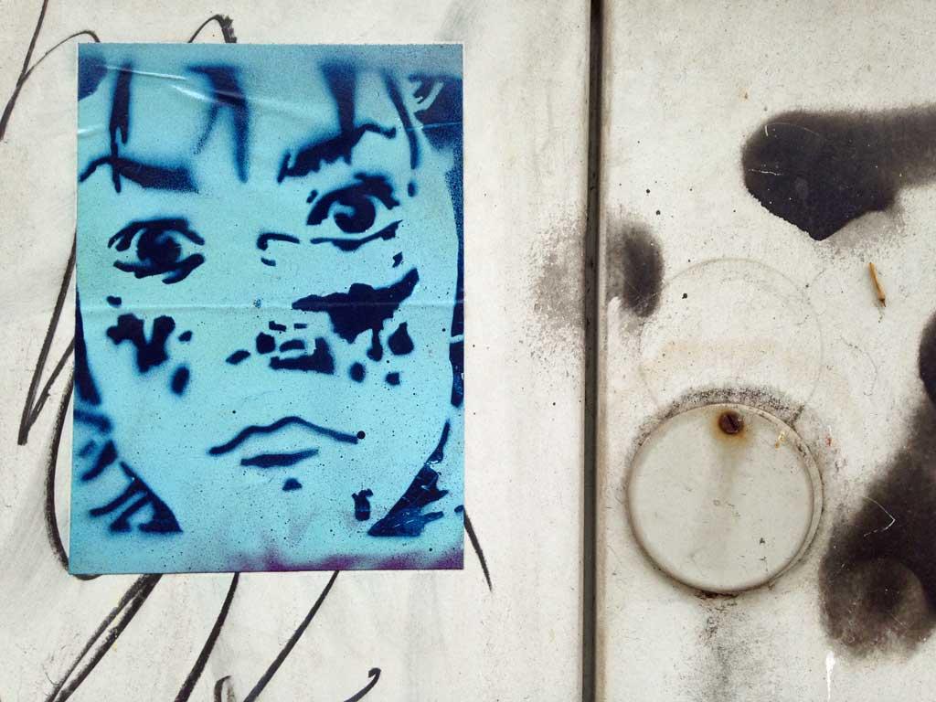 Zweifarbiger Aufkleber mit Schablonengraffiti-Motiv eines Gesichtes