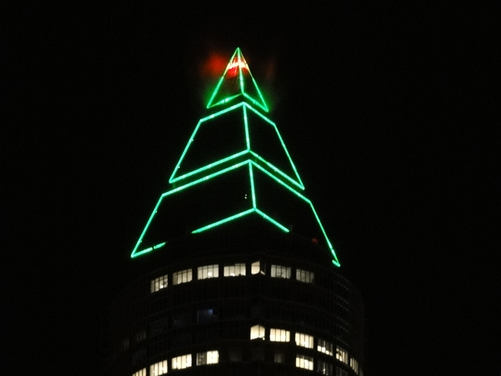 Grün beleuchtete Spitze des Messeturms in Frankfurt am Main