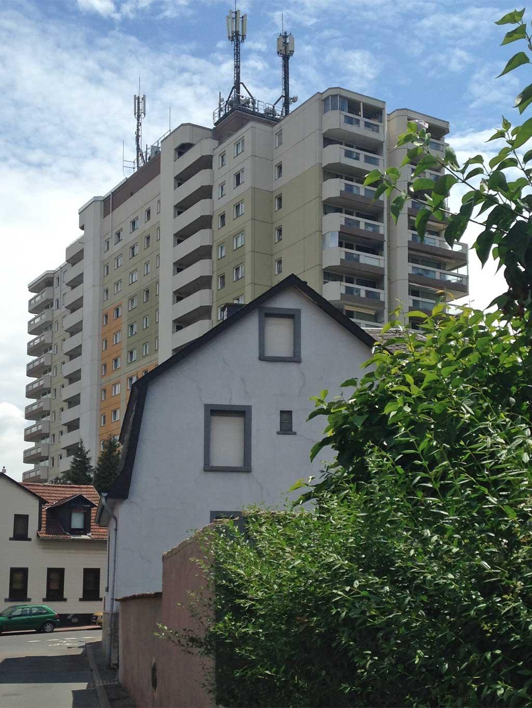 Kleines Haus im Schatten eines Wohnhochhauses