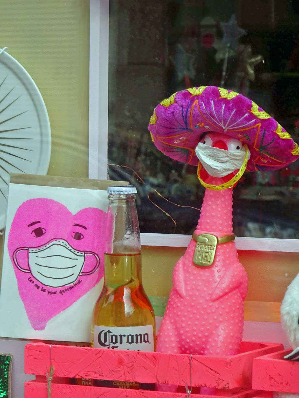 Ladengeschäft mit maskierten Figuren und Corona-Bier