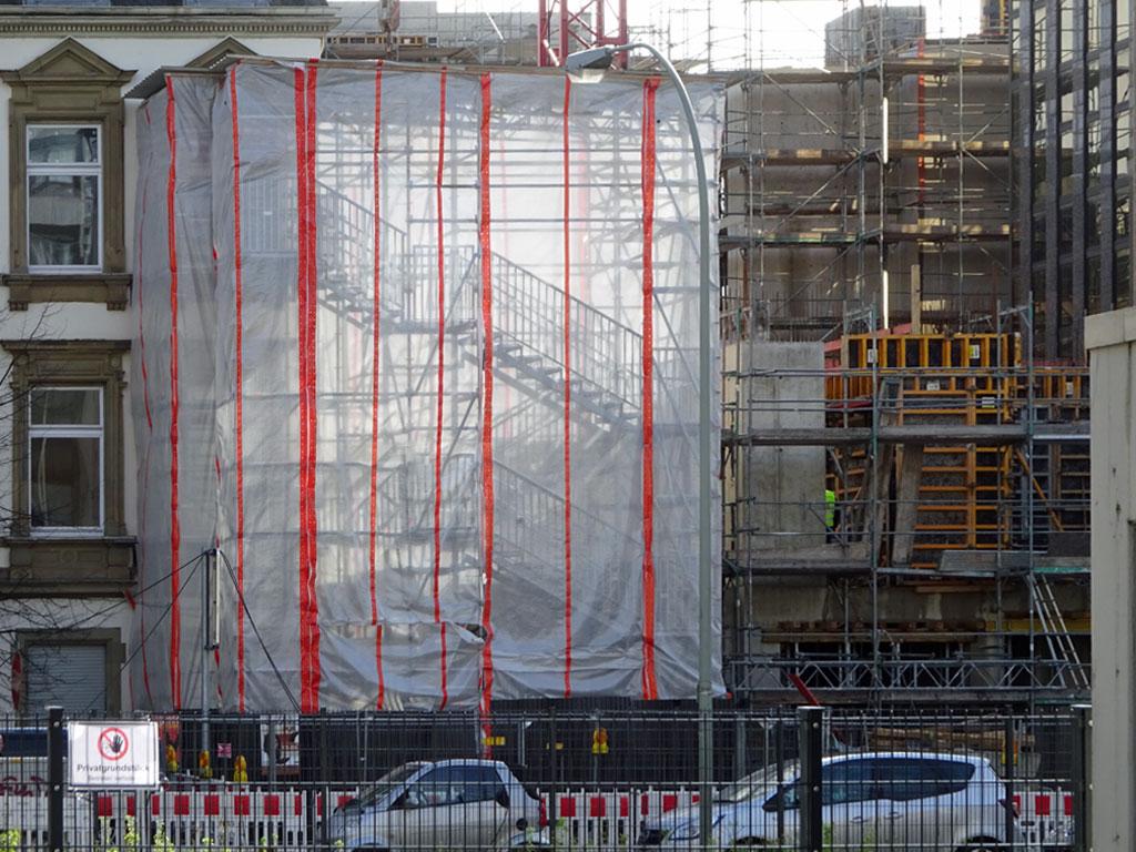 Licht und Schatten bei transparentem Fassadenschutz einer Baustelle in Frankfurt