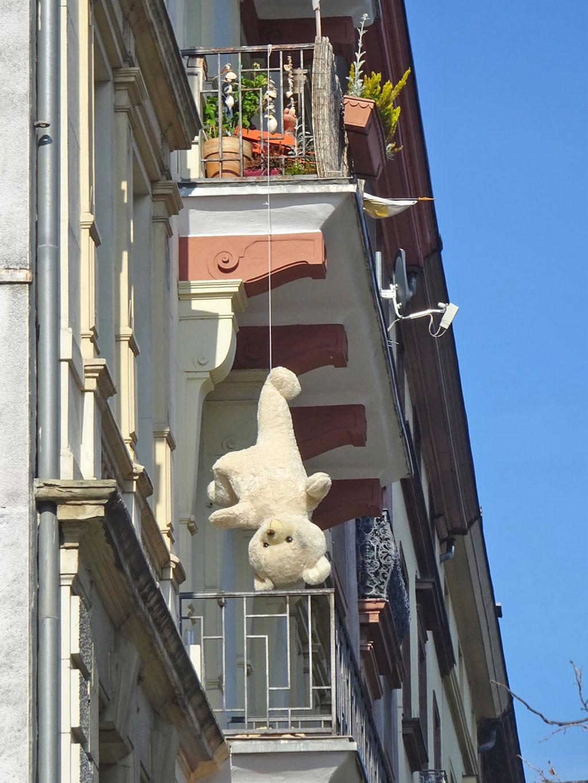Teddybär hängt kopfüber vom Balkon