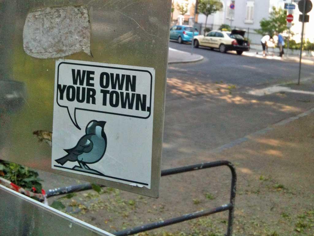 """Aufkleber mit Vogel und """"We own your town""""-Sprechblase"""