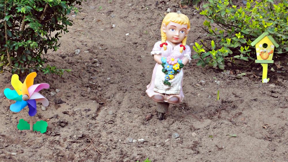 Windrad, Mädchen-Figur und Vogelhäuschen in einem Vorgarten im Nordend Frankfurts
